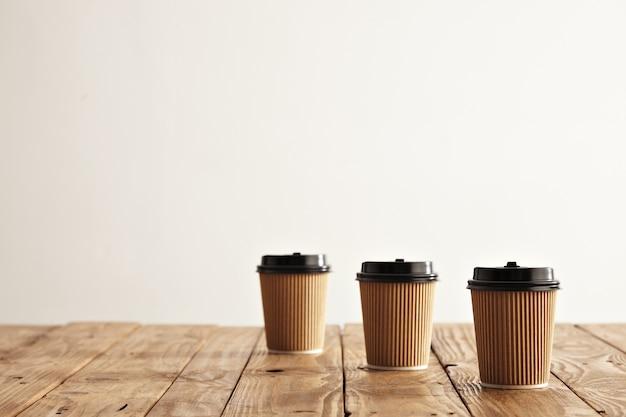 소박한 나무 테이블의 오른쪽에 고립 된 행에 3 개의 판지 종이 컵 무료 사진