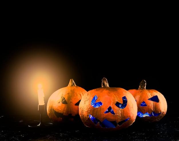 Tre intagliato zucca di halloween con brillante candelabro Foto Gratuite