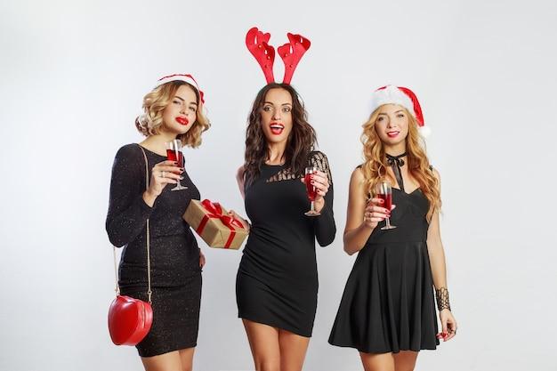 新年やクリスマスパーティーで過ごす3人の魅力的な女の子。シャンパンのグラスを保持しています。仮面舞踏会の帽子をかぶっています。 無料写真