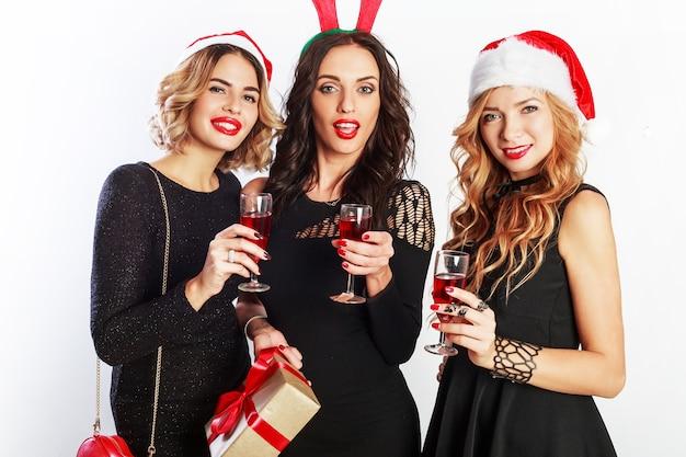 新年会に時間を費やしている3人の魅力的な女の子。シャンパンのグラスを保持しています。仮面舞踏会の帽子をかぶっています。 無料写真