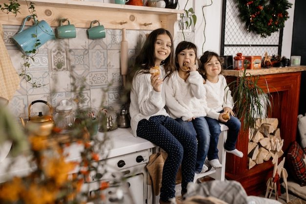 Three charming little girls in white sweaters and blue jeans play on an old-fashioned kitchen Free Photo