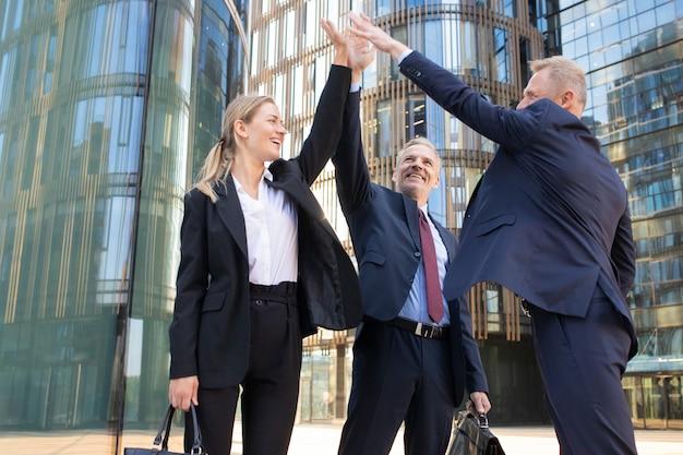 5人を与えると笑顔の3人の陽気なビジネスマン。自信を持って幸せな同僚が取引の成功を祝い、屋外で立ち上がって手を挙げます。チームワークとパートナーシップの概念 無料写真