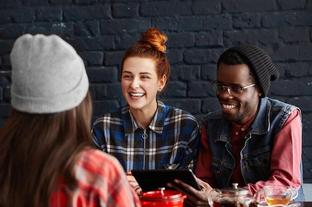 3人の陽気な学生がレストランで食事をし、お互いに話し、楽しんでいる 無料写真