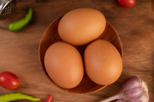 Три куриные яйца на тарелку с чесноком помидоры и перец чили. Бесплатные Фотографии