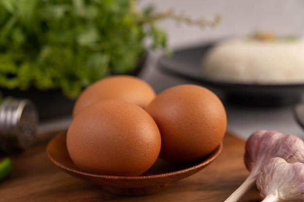 Три куриные яйца на тарелку с чесноком. Бесплатные Фотографии