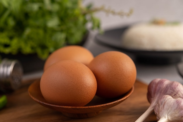Three chicken eggs on the plate with garlic. Free Photo