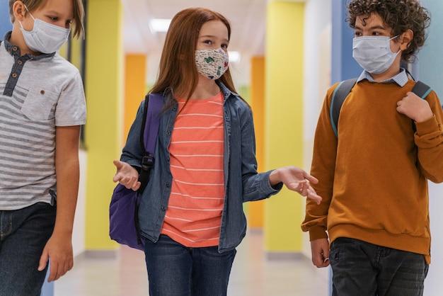 Трое детей в школьном коридоре с медицинскими масками Premium Фотографии