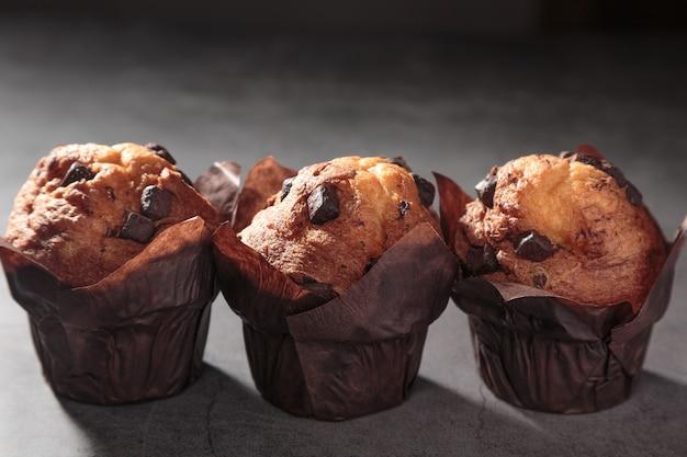 Три шоколадных маффина на темном фоне. Premium Фотографии