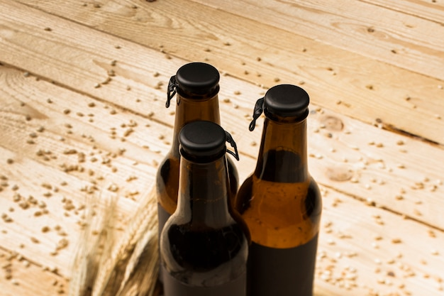 Three closed beer bottles and ears of wheat on woodgrain Free Photo