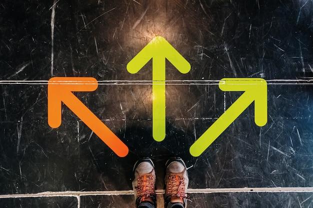 地面にある3色の矢印は、ブーツを履いた男性の足を指しています。 Premium写真
