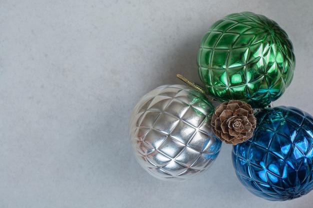 흰색 바탕에 한 Pinecone와 3 개의 화려한 크리스마스 공. 고품질 사진 무료 사진