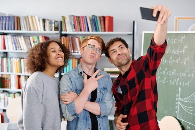 Трое современных товарищей по команде позируют для селфи перед смартфоном в библиотеке или классе Premium Фотографии