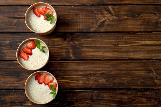 Три бумажных стаканчика крафт с пудингом из тапиоки с растительным молоком Premium Фотографии