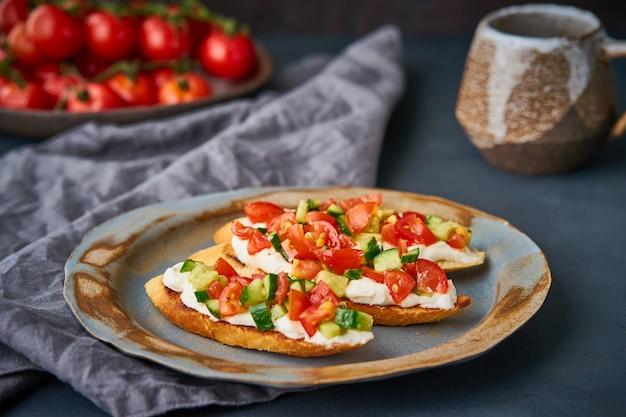 Three crostini, traditional italian sandwich with tomatoes and cucumbers Premium Photo