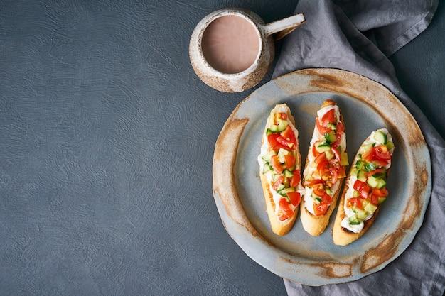Three crostini, traditional italian sandwich with tomatoes and cucumbers. Premium Photo