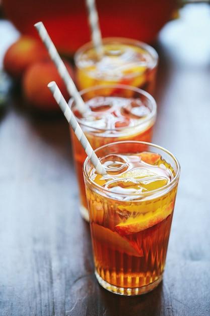 Три чашки персикового сока на столе Бесплатные Фотографии