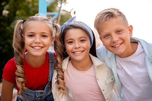 Three cute friends smiling on the playground Free Photo
