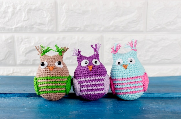 Three cute handmade knitted owls toys Premium Photo