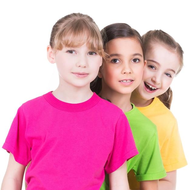 화려한 티셔츠에 세 귀여운 작은 귀여운 웃는 여자는 흰 벽에 서로 뒤에 서있다. 무료 사진