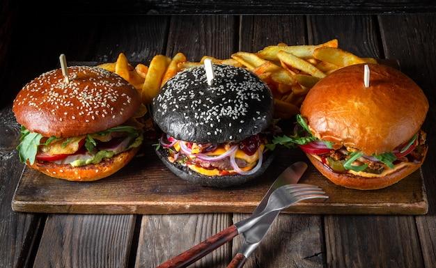 Три разных гамбургера в ряд на деревянной доске на темной поверхности Premium Фотографии