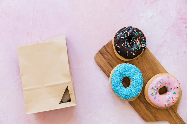 Three different type of donuts near parcel on pink background Photo