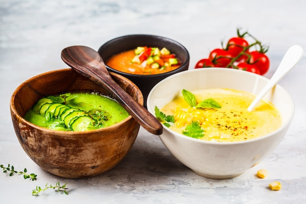 Three different vegetable cream soups in bowls on gray  corn, cucumber and gazpacho soups, Premium Photo