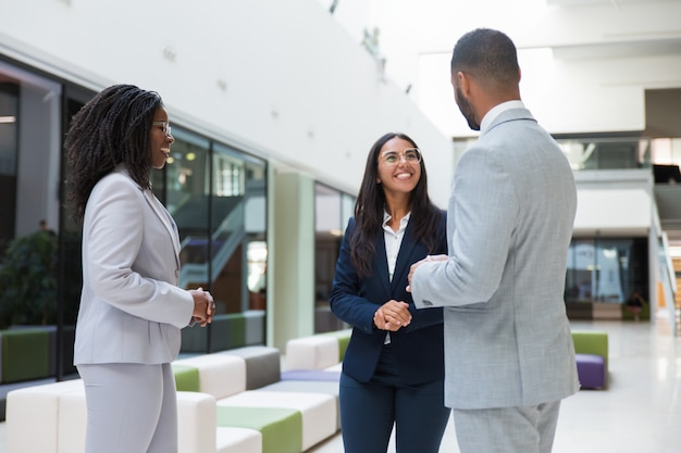 Three diverse business partners meeting in office hall Free Photo