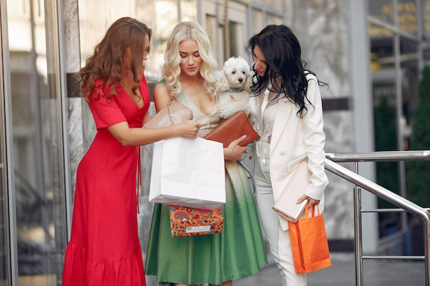 Three elegant women with shopping bags in a city Free Photo