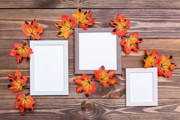 Three empty photo frame on a brown wooden table surrounded by orange maple leaves. Premium Photo