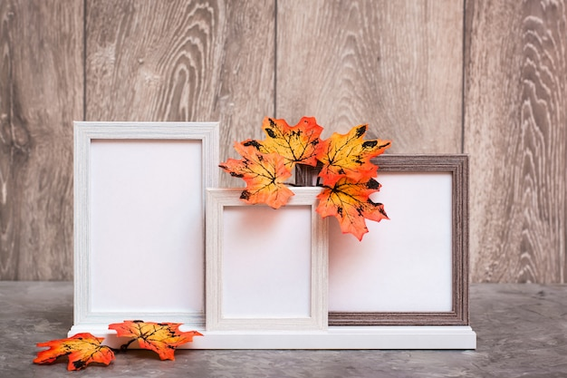 Three empty photo frames on a stand and orange maple leaves stand on a table. white-orange-beige color scheme. copy space Premium Photo
