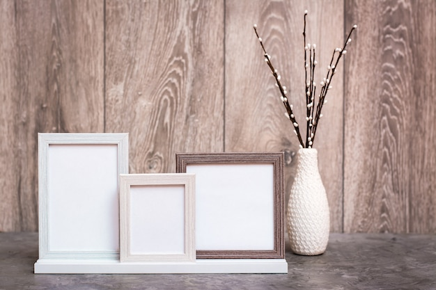Three empty photo frames on the stand and a vase with artificial willow branches are on the table. white-gray-beige color gamut. copy space Premium Photo