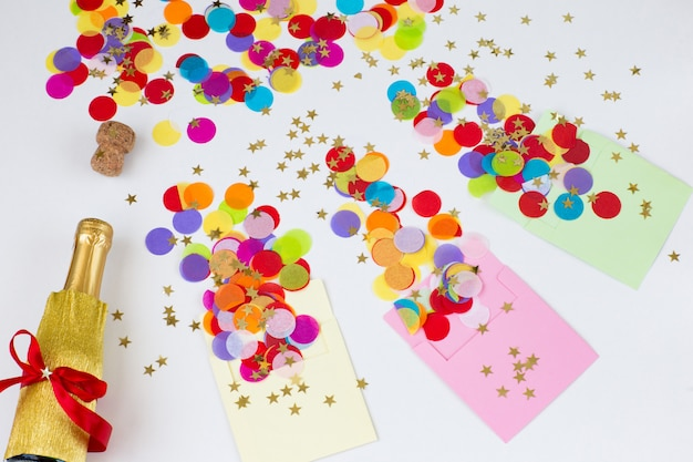Three envelopes on a white background, colored confetti are flying from them, a bottle of champagne Premium Photo