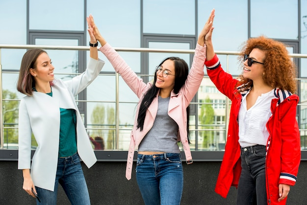 Three fashionable female friends giving high five at outdoors Free Photo