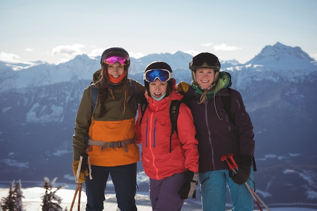 Three female skiers standing together on snow covered mountain Free Photo