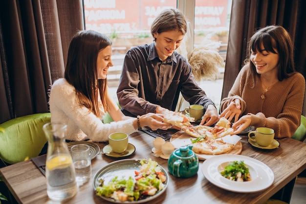 Tre amici mangiano insieme la pizza in un caffè Foto Gratuite