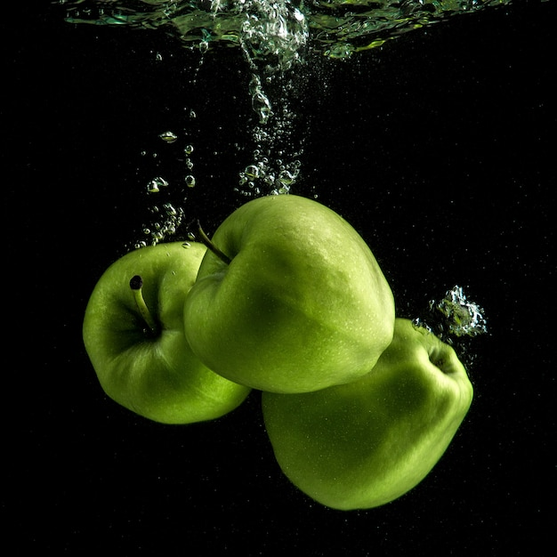 Three fresh green apples in the water Free Photo