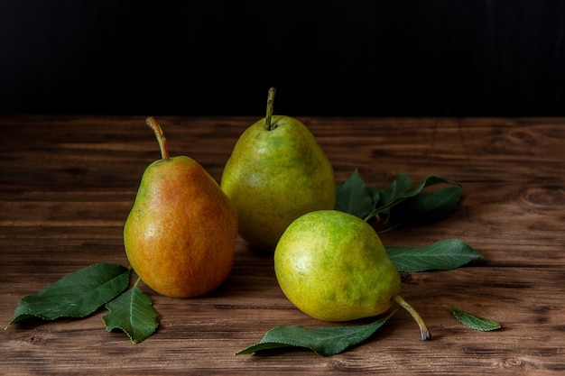 Three fresh pears with leaves lie on a wooden table Premium Photo