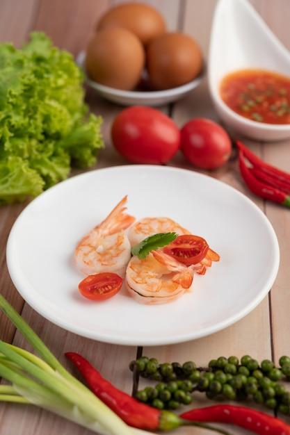 3つの新鮮なエビと木製の白い皿に半分のトマト。 無料写真