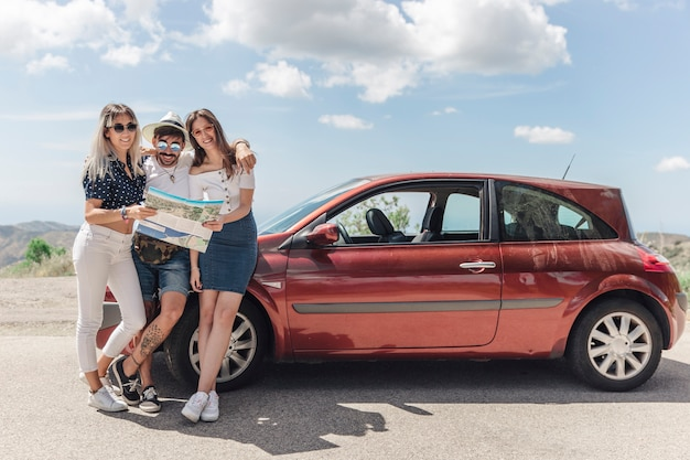 Three friends holding map standing near the modern car on road Free Photo