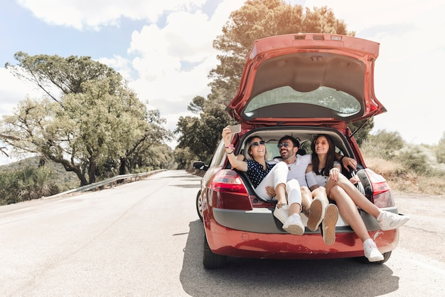 Three friends sitting together in car trunk taking self portrait on the road Free Photo