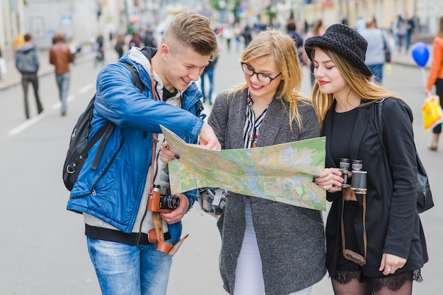 Three friends with map on street Free Photo