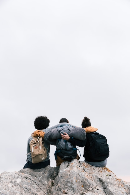 Three friends with their arms around sitting on the top of mountain Free Photo