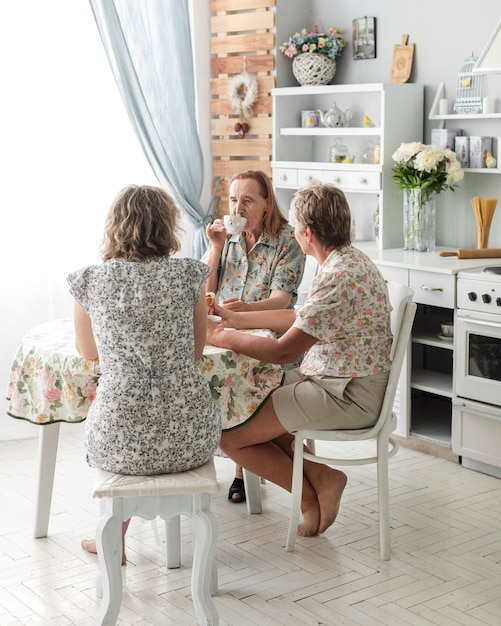 Three generation women drinking coffee together in kitchen Free Photo