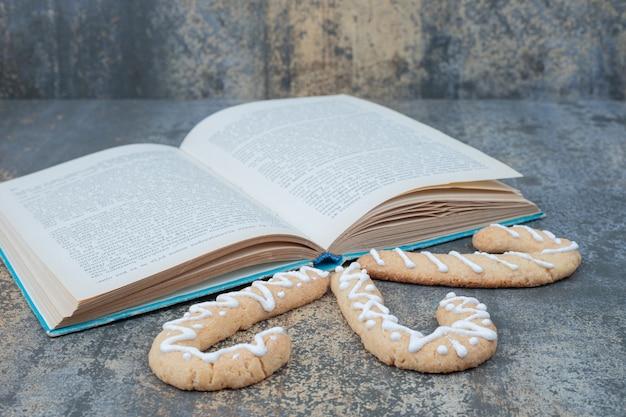大理石の背景に3つのジンジャーブレッドクッキーと開いた本。高品質の写真 無料写真