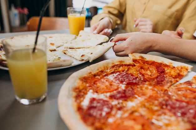 Three girl friends having pizza at a bar Free Photo