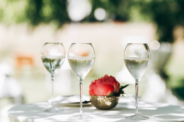 Three glasses with water and red peony stand on the table Free Photo
