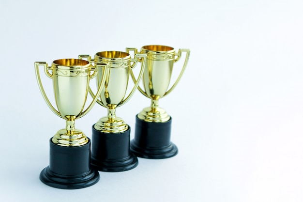 Three golden winner cups. competitions concept. Premium Photo