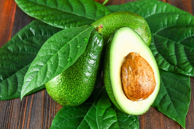 3 зеленых сырых зрелых плодоовощ авокадоа и отрезанная половина с костью с листьями на коричневом деревянном столе. Premium Фотографии