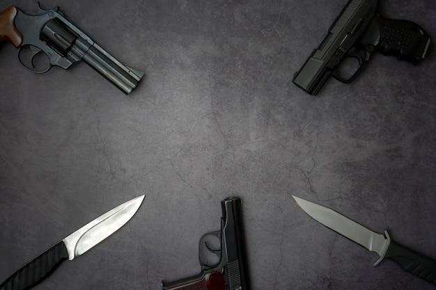 Три пистолета, пистолеты, армейские ножи крупным планом на сером фоне бетона. Premium Фотографии