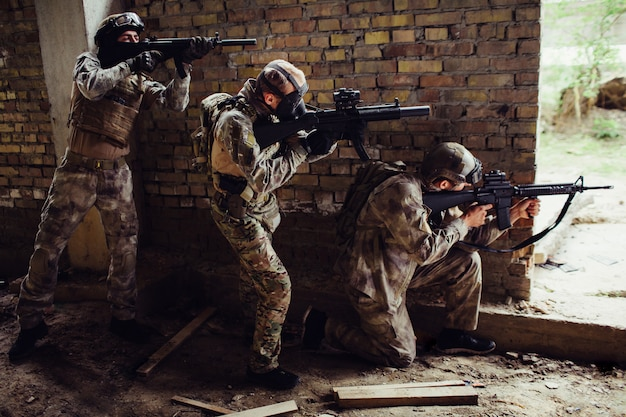 Three guys in ammunition are standing and hiding behind wall. first man is siting on his knees and targeting. other guys are standing behind each other. they have rifles in therir hands. Premium Photo